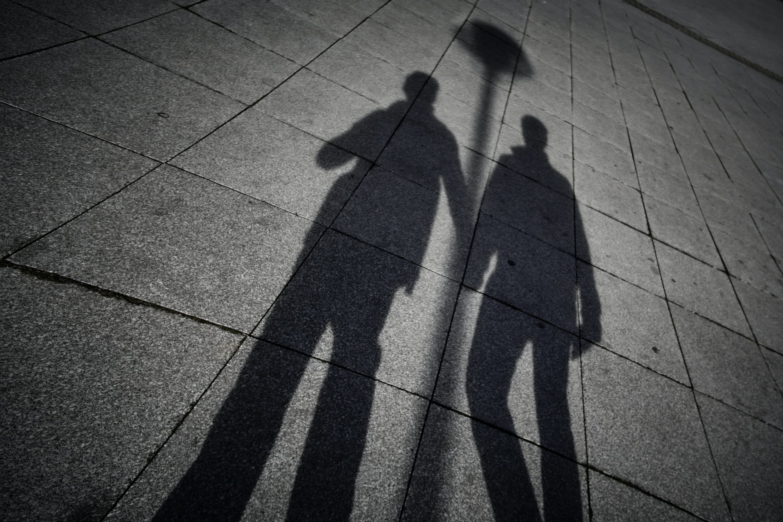 Shadow of two people holding hands